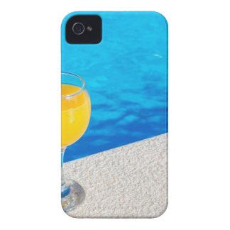 Glass with orange juice on edge of swimming pool iPhone 4 case
