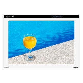 Glass with orange juice on edge of swimming pool laptop skins