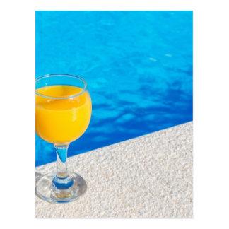 Glass with orange juice on edge of swimming pool postcard