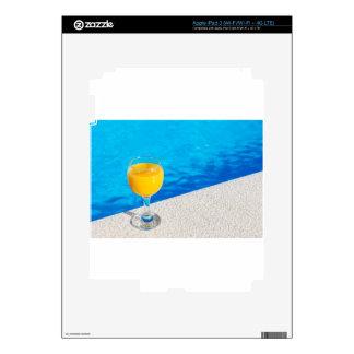 Glass with orange juice on edge of swimming pool skin for iPad 3