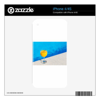 Glass with orange juice on edge of swimming pool skins for iPhone 4