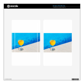 Glass with orange juice on edge of swimming pool skins for kindle fire