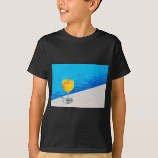 Glass with orange juice on edge of swimming pool T-Shirt