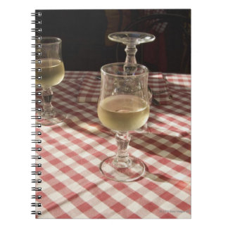 Glasses for water and wine on outdoor red spiral notebooks
