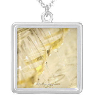 Glasses of white wine for wine tasting, close up square pendant necklace