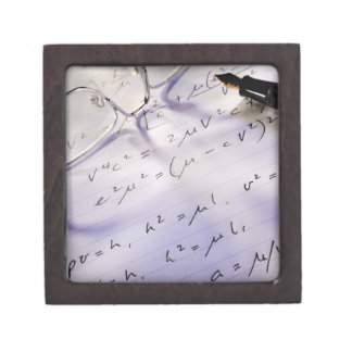 Glasses, pen and mathematical symbols on paper, gift box