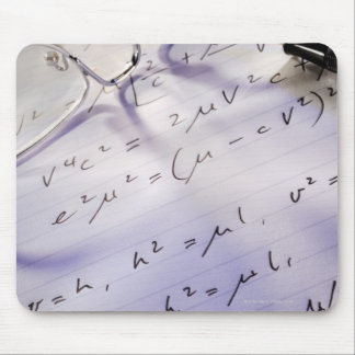 Glasses, pen and mathematical symbols on paper, mouse pad