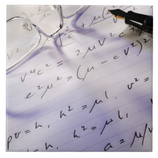 Glasses pen and mathematical symbols on paper tiles
