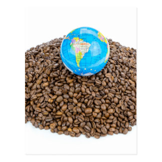 Globe with world on heap of whole coffee beans postcard