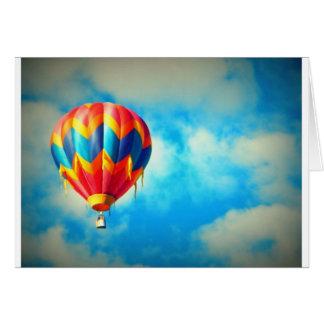 Globo del aire caliente en alto en el cielo azul tarjeta de felicitación