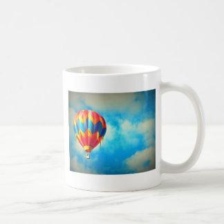 Globo del aire caliente en alto en el cielo azul taza de café