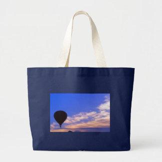 Globo del aire caliente en el amanecer bolsas