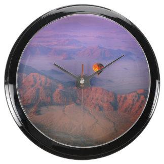 Globo del aire caliente sobre el desierto de reloj pecera