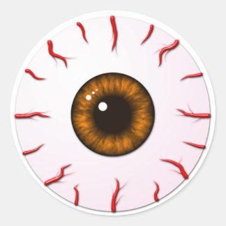 Globo del ojo con el iris anaranjado y las venas pegatina redonda