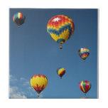 Globos coloridos del aire caliente en el cielo azulejo ceramica