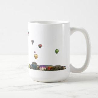 Globos de levantamiento sobre árboles y montañas taza de café