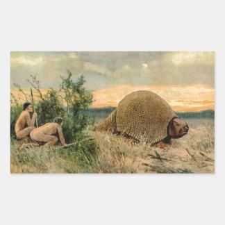 Glyptodon y hombres de cueva que cazan la imagen pegatina rectangular