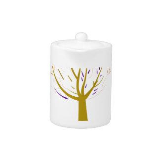 Gold tree on white teapot
