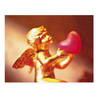 Golden angel holding pink heart, side view, soft postcard