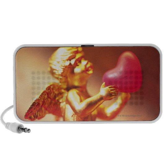 Golden angel holding pink heart, side view, soft speaker
