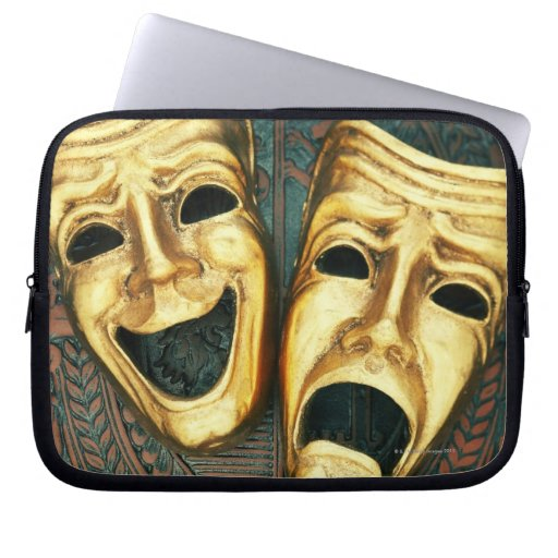Golden comedy and tragedy masks on patterned computer sleeves