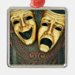 Golden comedy and tragedy masks on patterned metal ornament