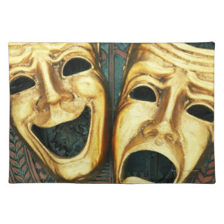 Golden comedy and tragedy masks on patterned cloth place mat