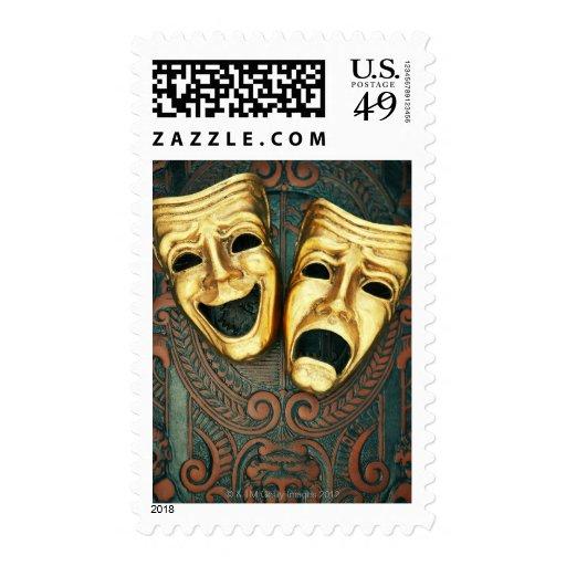 Golden comedy and tragedy masks on patterned stamp