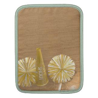 golden pom poms on gym floor iPad sleeve