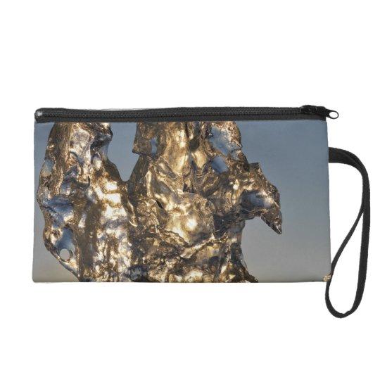 Golden sunrise seen through iceberg formation wristlet purse