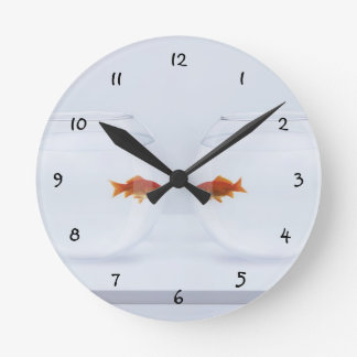 Goldfish in separate fishbowls looking face to fac round clock