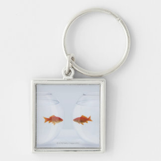 Goldfish in separate fishbowls looking face to keychain