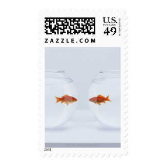 Goldfish in separate fishbowls looking face to stamps