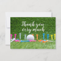 Golf ball and colourful tees are on green grass thank you card