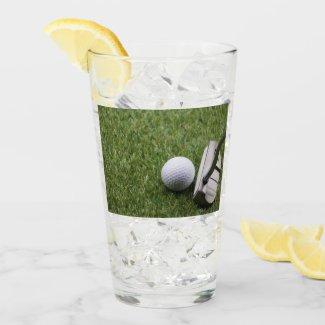 Golf ball and putter on green grass glass