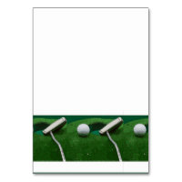 Golf ball and putter on green grass table number