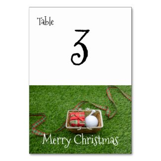 Golf ball and tee and Christmas ribbon on green Table Number