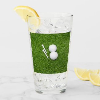 Golf ball and tee are on green grass glass