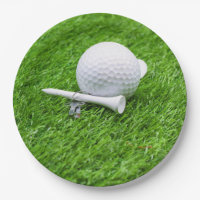 Golf ball and tee on green grass paper plate