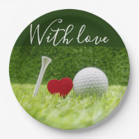Golf ball and tee on green grass with love paper plate