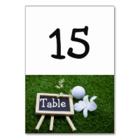 Golf ball and white orchid on green grass table number