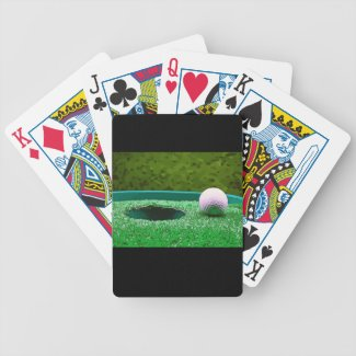 Golf ball next to hole bicycle playing cards