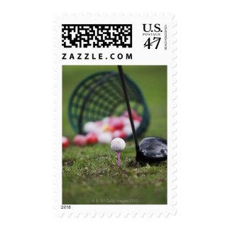 Golf ball on tee beside golf club postage