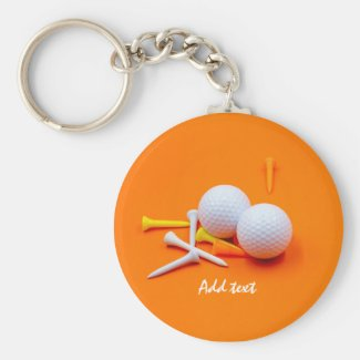 Golf ball white and yellow tees are on orange keychain