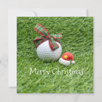 Golf ball with Christmas hat on green grass