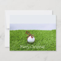 Golf ball with Christmas ribbon on green grass