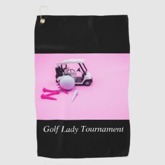 Golf ball with golf cart and pink tee on pink golf towel