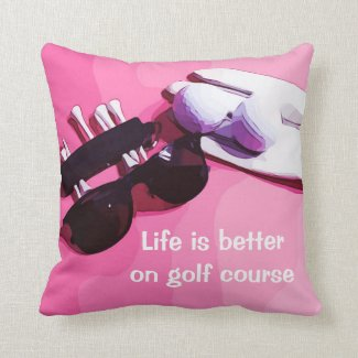 Golf ball with golf glove and tee on pink throw pillow