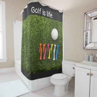 Golf ball with multi colour tees are on green shower curtain