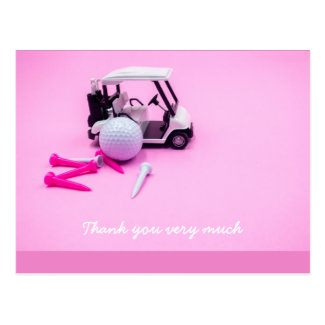 Golf ball with pink cart and white  tee on pink postcard